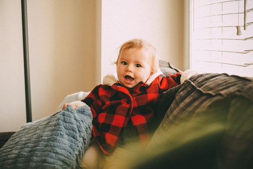 baby smiling in a plaid sweater on a couch in Napa Ca