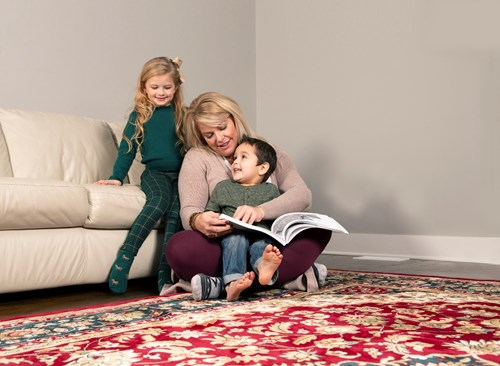 a mom son and daughter reading a book on a red oriental rug in a living room in Napa CA